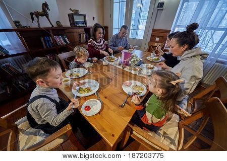 Three adults and four children eat sitting at wooden table in room.