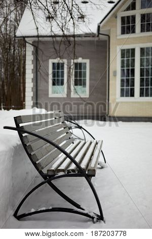 Bench in courtyard near house in winter.