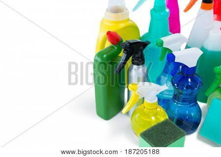 High angle view of colorful spray bottles with sponges and gloves against white background