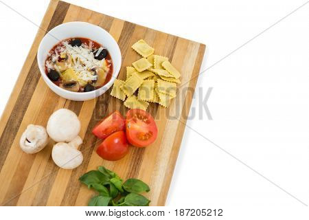 High angle view of food in bowl by ravioli and vegetables on cutting board