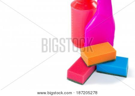 Close up of colorful sponges with bottle against white background