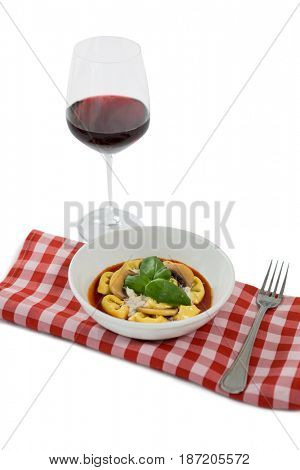 High angle view of cooked tortelloni on napkin by wineglass against white background