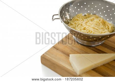 Close up of spaghetti in colander by cheese on cutting board against white background