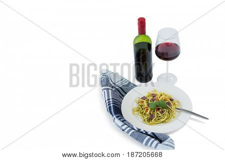 High angle view of pasta served in plate by wineglass against white background