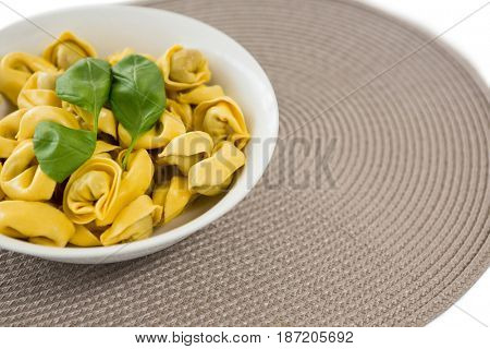 High angle view of cooked pasta served in bowl on place mat over white background