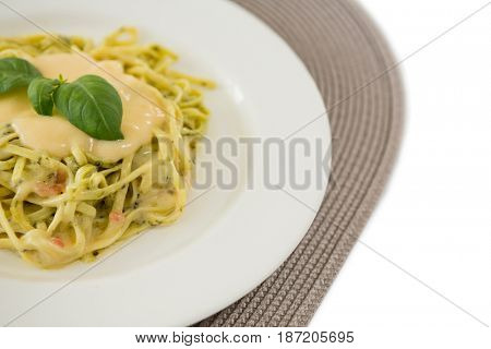 Close up of cooked pasta served with sauce in plate on place mat aganinst white background