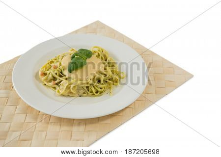Close up of fettuccine served in plate on place mat against white background