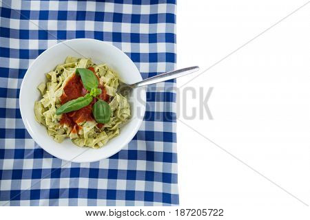 Close up of pasta served in bowl on napkin against white background