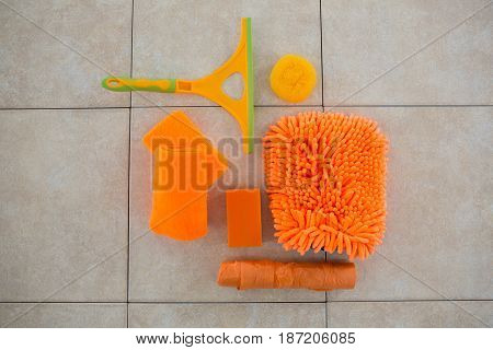 Overhead view of orange cleaning products on tiled floor