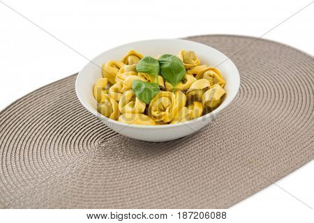 Close up of cooked pasta served in bowl on place mat over white background
