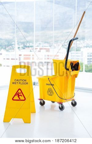 Sigh board with mop bucket in room against glass