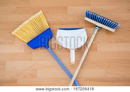 Overhead view of brooms with dustpan on hardwood floor