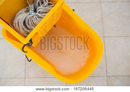 Overhead view of mop bucket on tiled floor