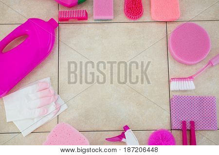 Overhead view of cleaning products arranged on tiled floor