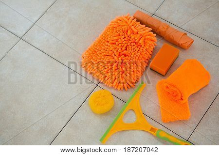High angle view of orange cleaning products on tiled floor