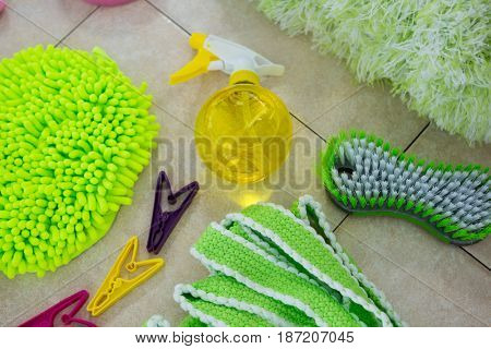 Overhead view of sponges and cleaning products on tiled floor