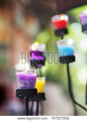 Close up candles in glass on black metal stand
