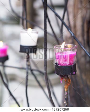 Close up candles in glasses on black metal stand