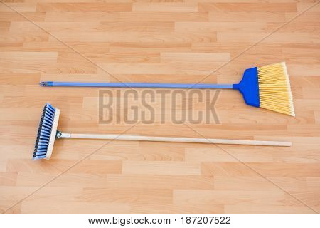 Hgh angle view of long handle brooms on hardwood floor poster