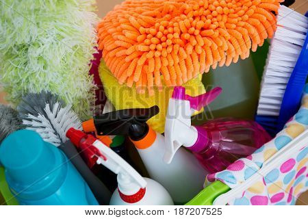 Close up of duster with spray bottles and cleaning equipment in bucket