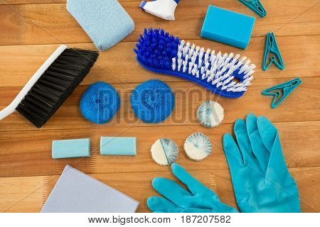 HIgh angle view of gloves and brush with clothespin on wooden table