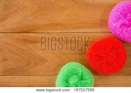 HIgh angle view of plastic sponge on wooden table