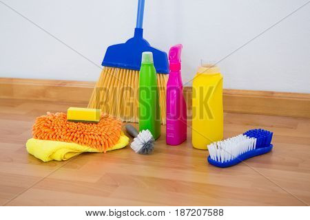 Chemical bottles by brush and sponges with broom on floor against wall