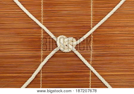 Knot of rope with four ends on a wooden background