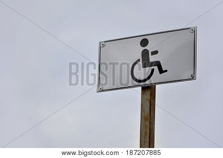 A Road Sign Indicating The Crossing Of A Road For Disabled People. White Road Sign With A Picture Of