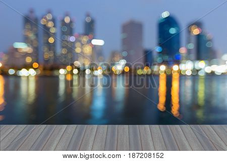 Opening wooden floor Night twilight blurred bokeh light city office and reflection abstract background