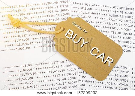 Saving for buy car wording with paper tag on account book background Car finance money concept.
