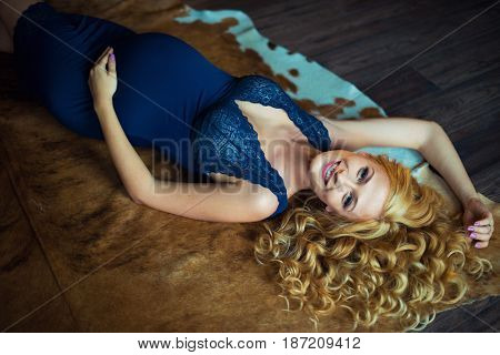 A stunningly beautiful red-haired pregnant girl lies on the floor. A gentle photo of a pregnant woman. View from above