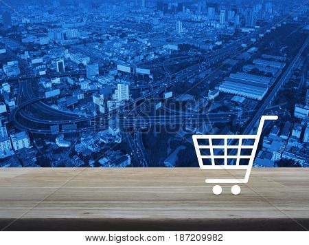 Shopping cart icon on wooden table over aerial of modern city tower street and expressway Shop online concept
