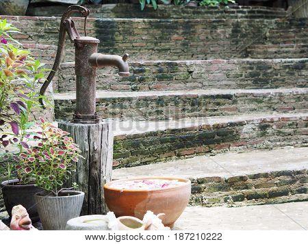 Vintage rusty hand water pump in the garden