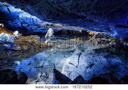 the slope of the mountain with the reflection in the water inside a fantastic cave. Kungur In The Urals