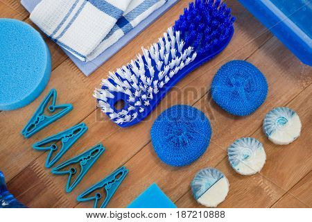 Overead view of brush and clothespin with sponge on wooden table