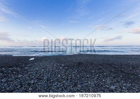 Small ice on black rock sand beach seacoast skyline Iceland natural landscape background