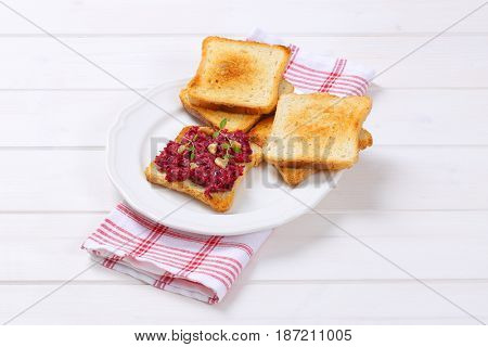 toasts with fresh beetroot spread on white plate