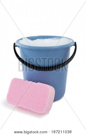 Close up of sponge by bucket containing soap sud against white background
