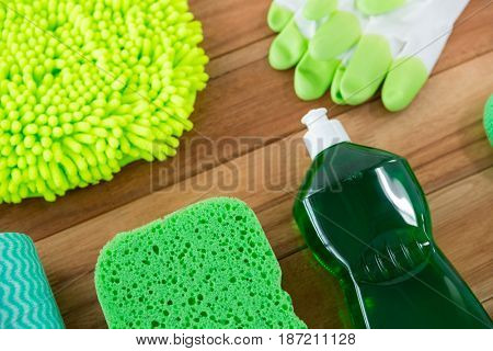 High angle view of chemical bottle with sponge and glove on wooden table