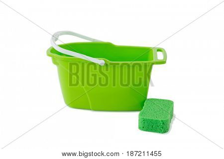 Close-up of green bucket with cleaning sponge against white background