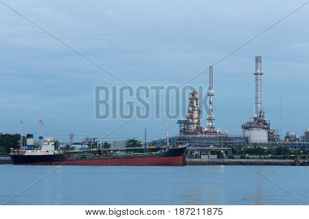 Oil tank ship over petrol refinery background river front at twilight