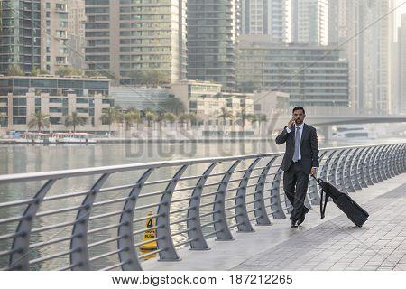 Businessman with a suitcase speaking ona phone in Dubai Marina UAE