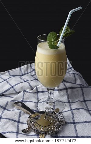 Cocktail of piña colada with mint next to cocktail accessories on a cloth and the black background
