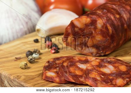 Closeup view of the sliced hot sausage Chorizo tomatoes garlic and whole black pepperon the olive tree desk.