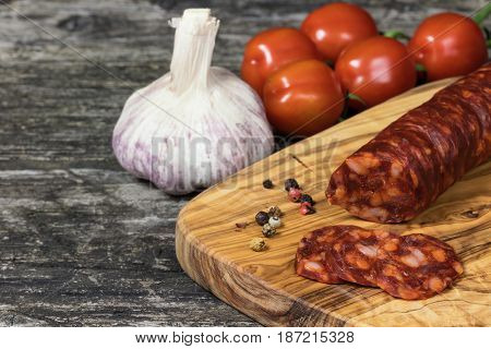Sliced hot sausage Chorizo tomatoes and garlic bulb on the old wooden desk.
