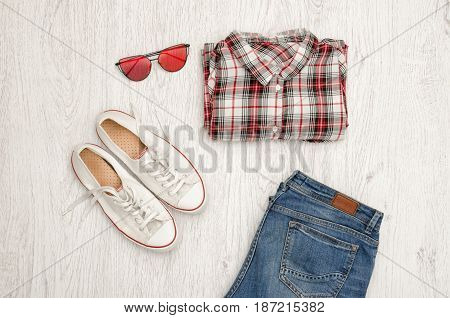 Red And White Plaid Shirt, Glasses, Sneakers And Jeans. Wooden Background. Fashionable Concept, Top