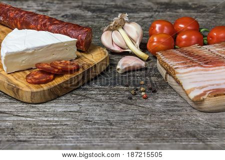 The old wooden desk with hot sausage Chorizo tomatoes garlic bulb and a piece of the Petite Brie cheese. Free place for your text is at the bottom of the photo.