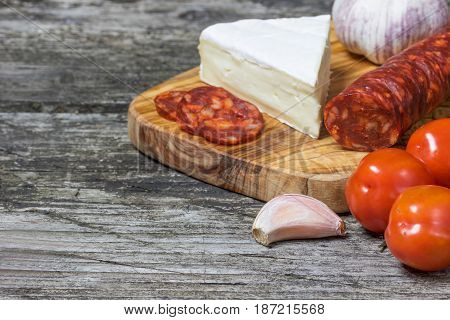 Closeup view of the old wooden desk with hot sausage Chorizo tomatoes garlic and a piece of the Petite Brie cheese.