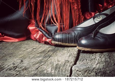 Clothing for Flamenco dance. Black shoes red scarf with tassels are on the old wooden desk. Edited as a vintage photo with dark edges.